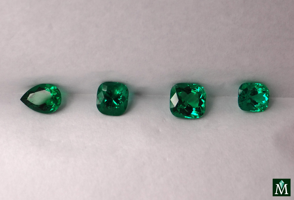 Cushion and drop parcel of emeralds